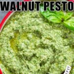 fresh basil walnut pesto in bowl with wooden spoon with text overlay