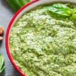 Basil Walnut Pesto in a bowl with wooden spoon