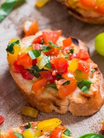 Rainbow colored fresh tomato bruschetta with fresh basil leaf