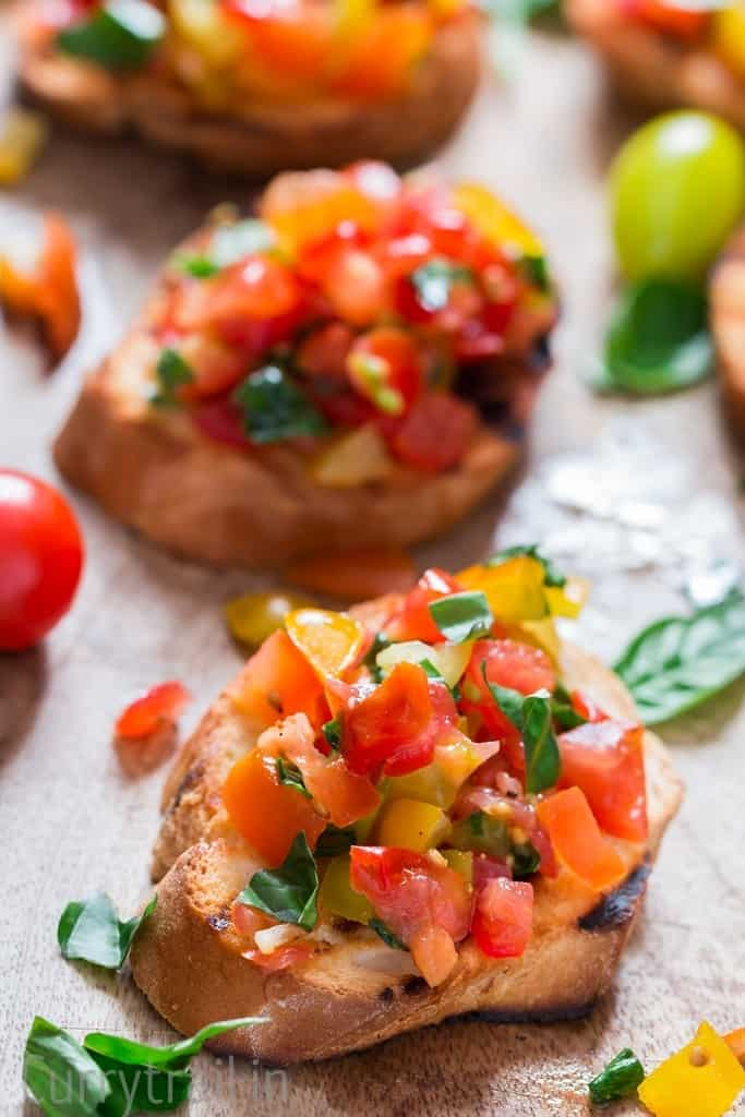 Wooden platter with fresh tomato bruschetta lined up