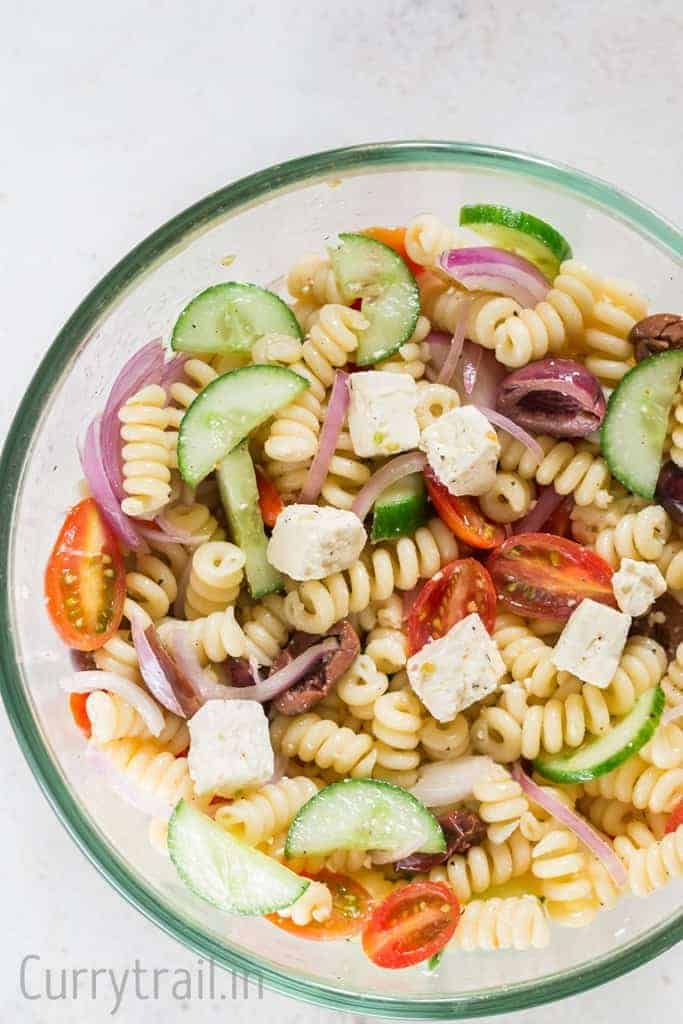 Greek pasta salad in glass salad bowl