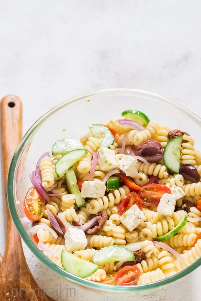 a mix of pasta vegetables and feta cheese in glass bowl with wooden spoon on side