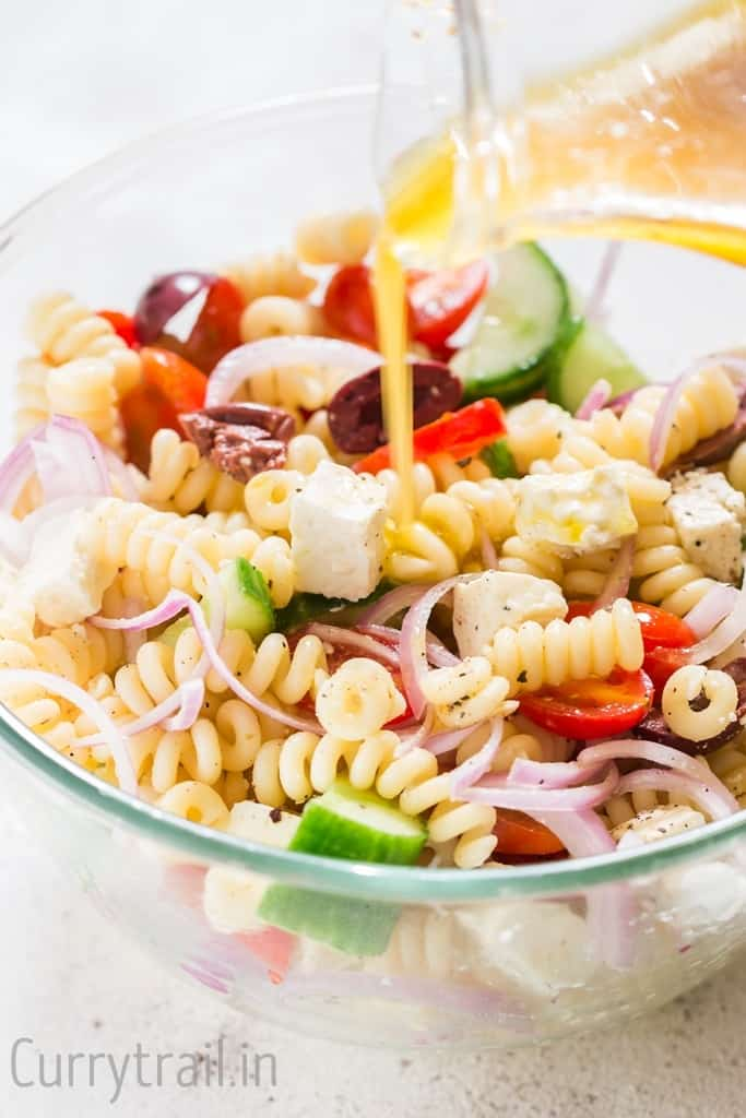 Red wine vinaigrette salad dressing poured over Greek pasta salad