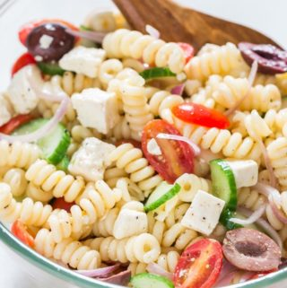 Greek pasta salad in a bowl with wooden spatula