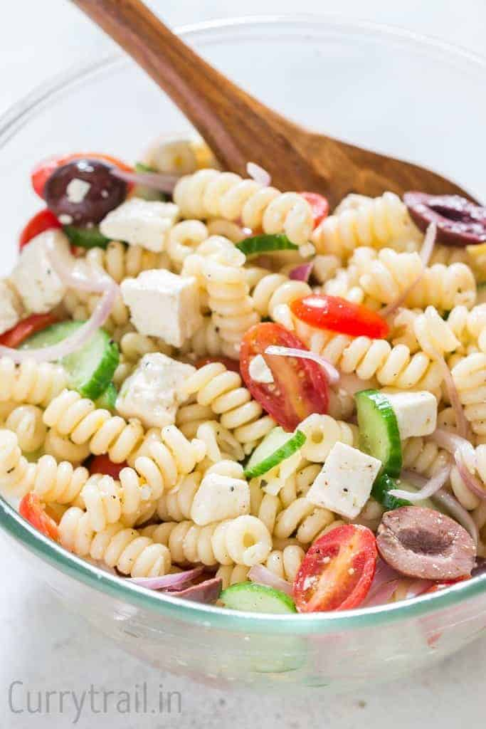 Greek pasta salad in glass bowl with wooden spatula