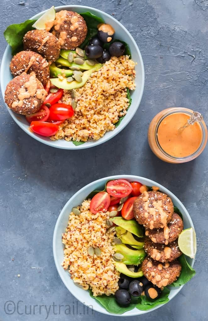 2 blue bowls having falafel, quinoa, vegetables all arranged for Mediterranean Vegan Buddha Bowl