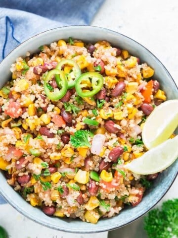 Mexican quinoa salad with lime wedges and jalapeno slices in a blue bowl