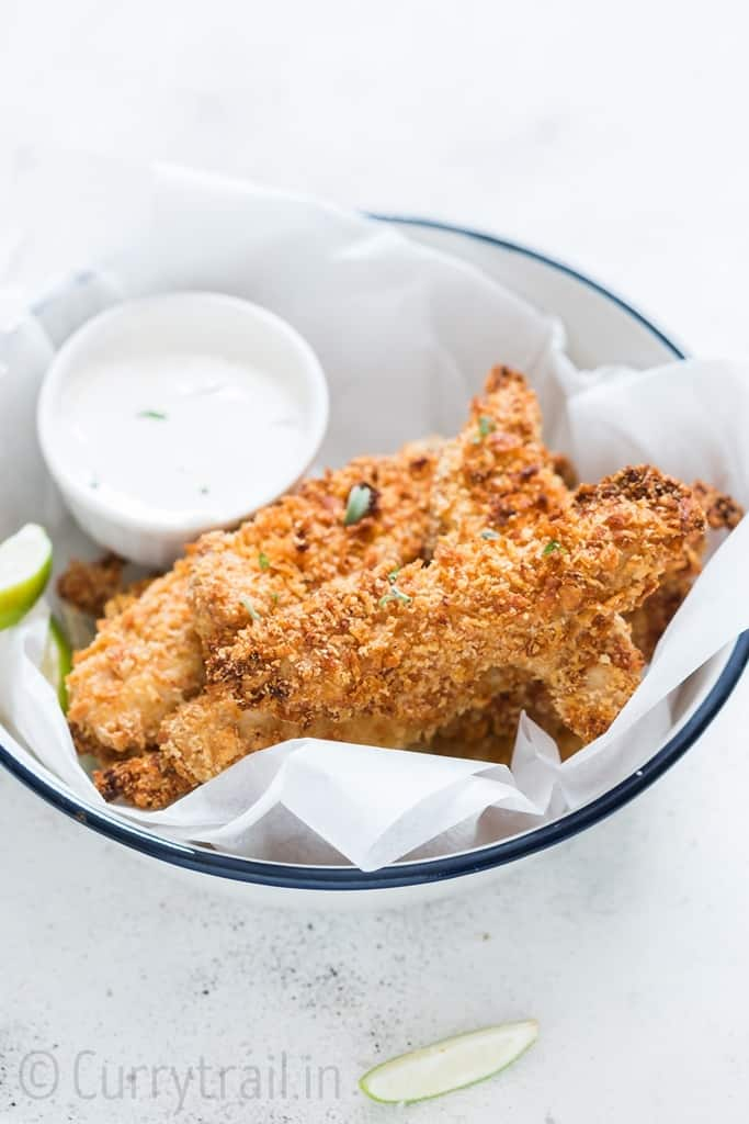 Crispy Parmesan crusted oven baked chicken tenders served on a white plate with ranch dip on sides
