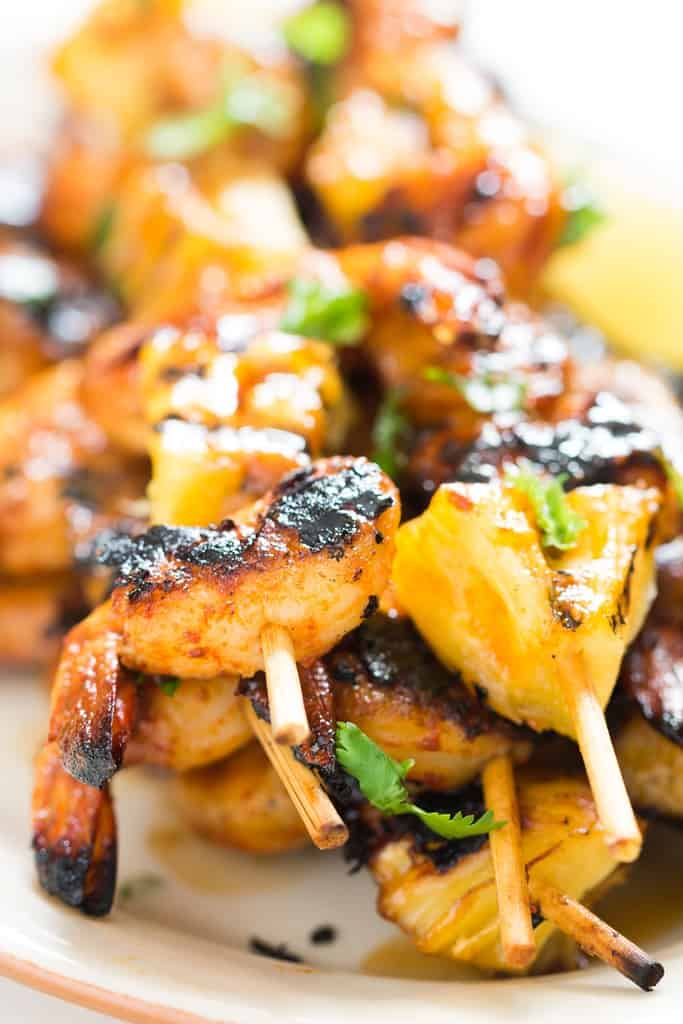 pineapple and shrimp skewered into bamboo sticks and grilled over BBQ with cilantro leave sprinkled on top served on white oval plate