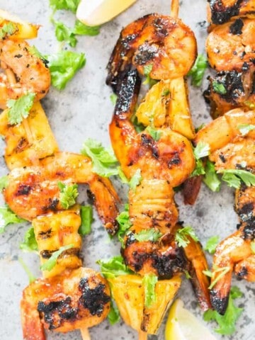 pineapple shrimp skewers with teriyaki sauce with cilantro sprinkled on top