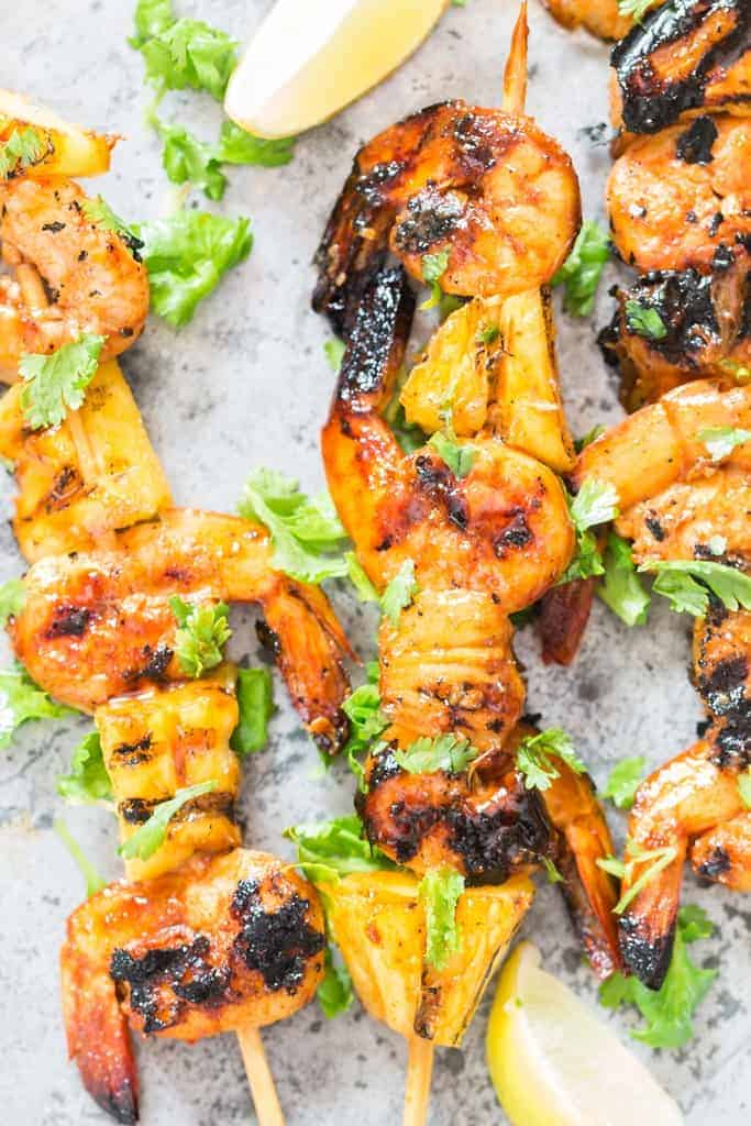 pineapple and shrimp skewered into bamboo sticks and grilled over BBQ placed on baking sheet with lemon wedges and cilantro leaves on top