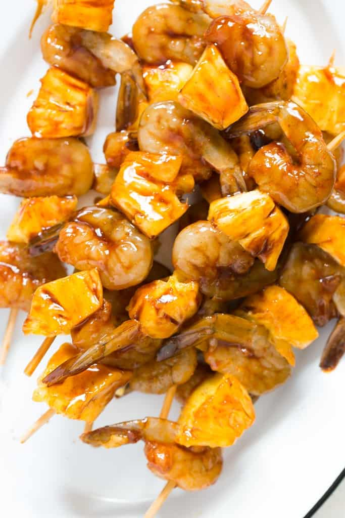 marinated pineapple and shrimp skewers on bamboo stick on white plate