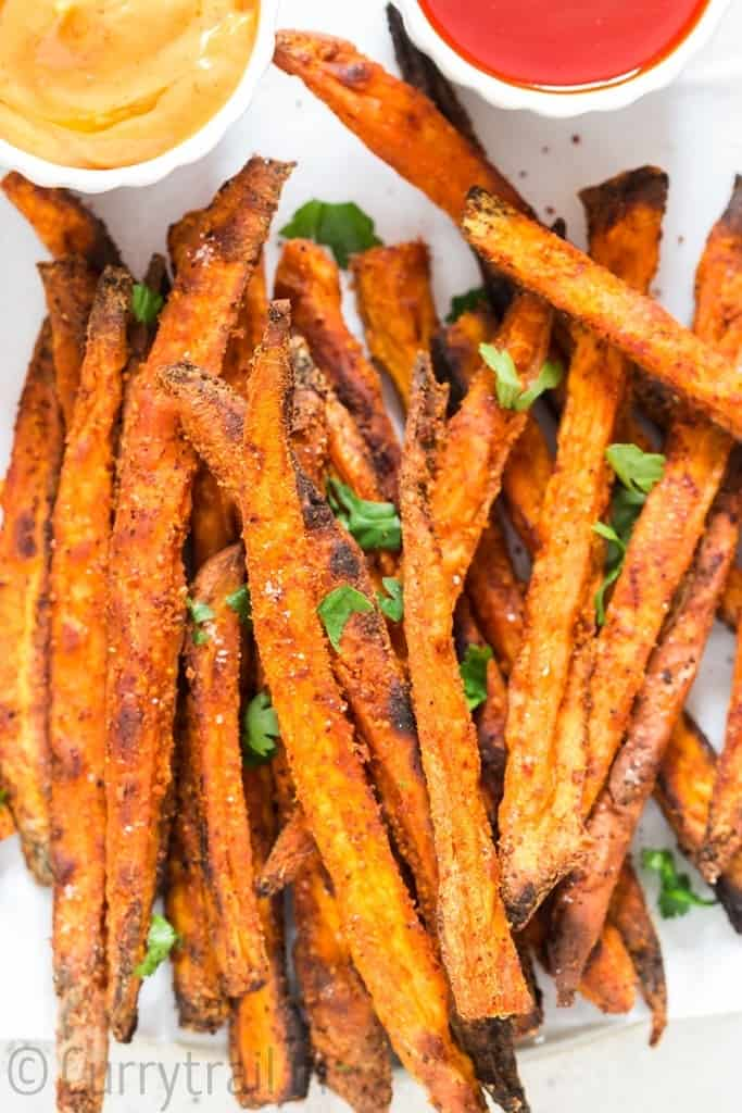baked sweet potato fries sprinkled with parsley on white plate with two dipping sauces on side