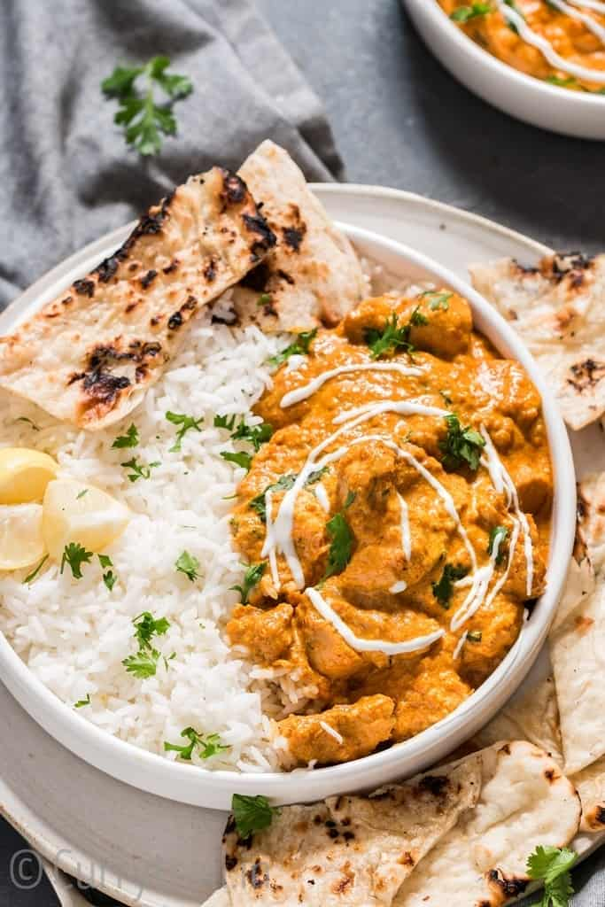 Instant pot butter chicken in white plate with rice and naan