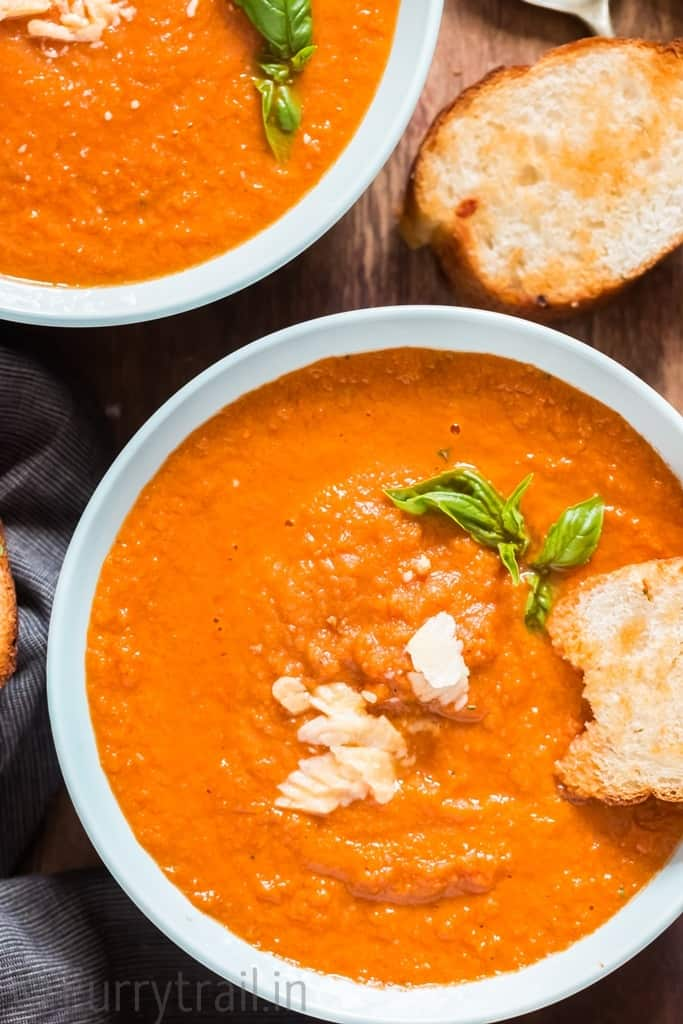 close up of roasted tomato basil soup with bread on side