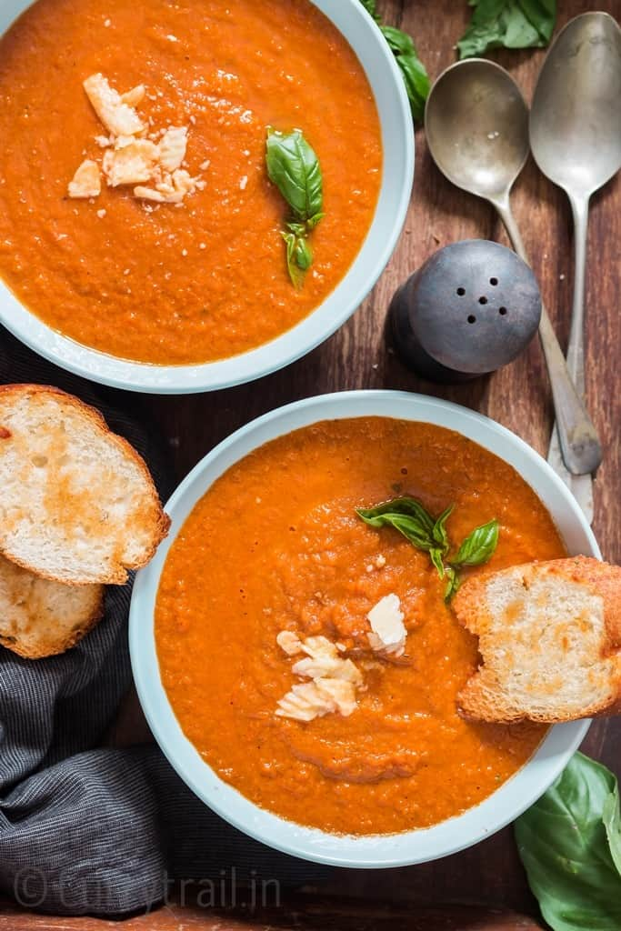 two bowls of roasted tomato basil soup with pepper shaker on the side