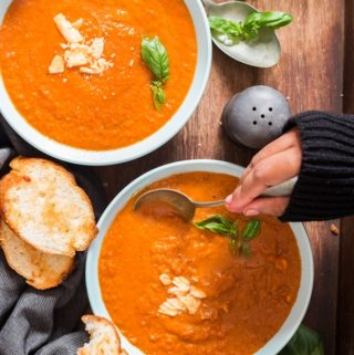 roasted tomato basil soup in 2 blue ceramic bowls with garlic bread on top