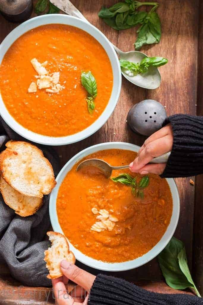 roasted tomato basil soup served in two ceramic bowls with bread on side