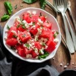 Watermelon and feta salad with basil leaves served in white bowl