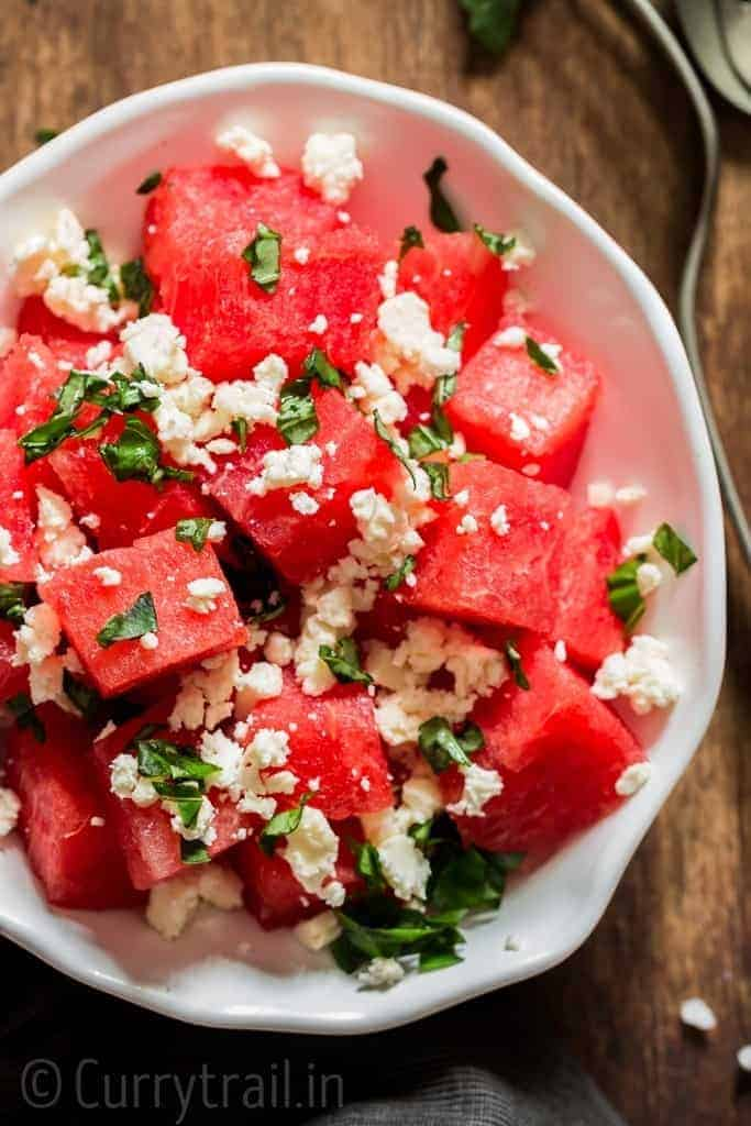 Watermelon feta salad with basil leaves served in white bowl