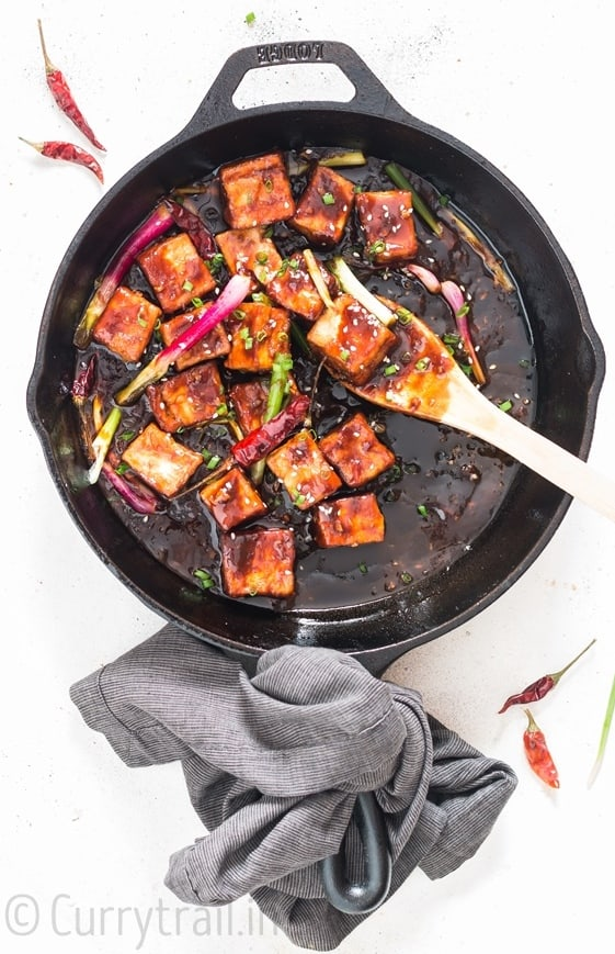 general tso's tofu cooked in cast iron pan with napkin tied to handle
