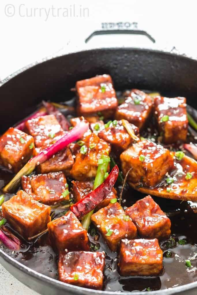 general tso's tofu cooked in cast iron pan with wooden spatula