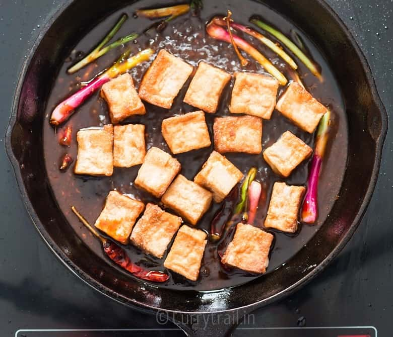 fried tofu cubes added to cast iron pan for general tso's tofu