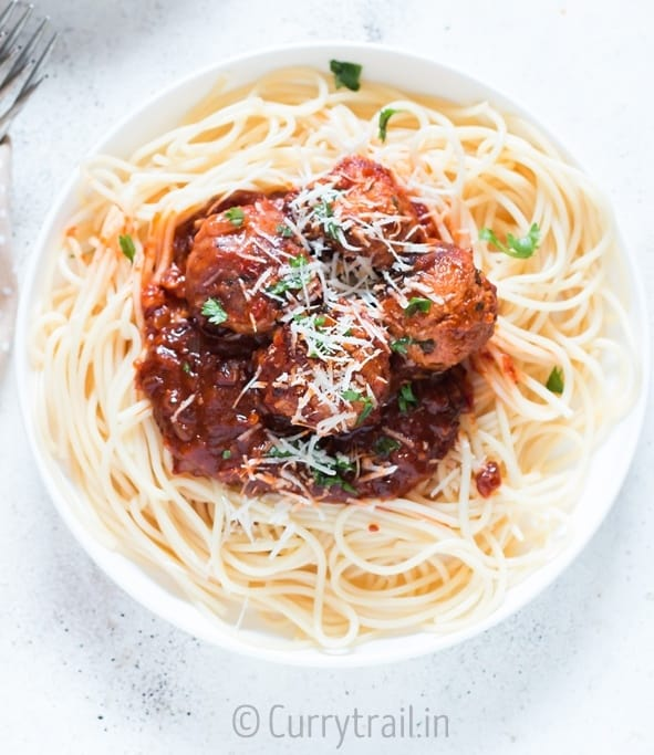 instant pot chicken Parmesan meatballs served on spaghetti in 2 white plates