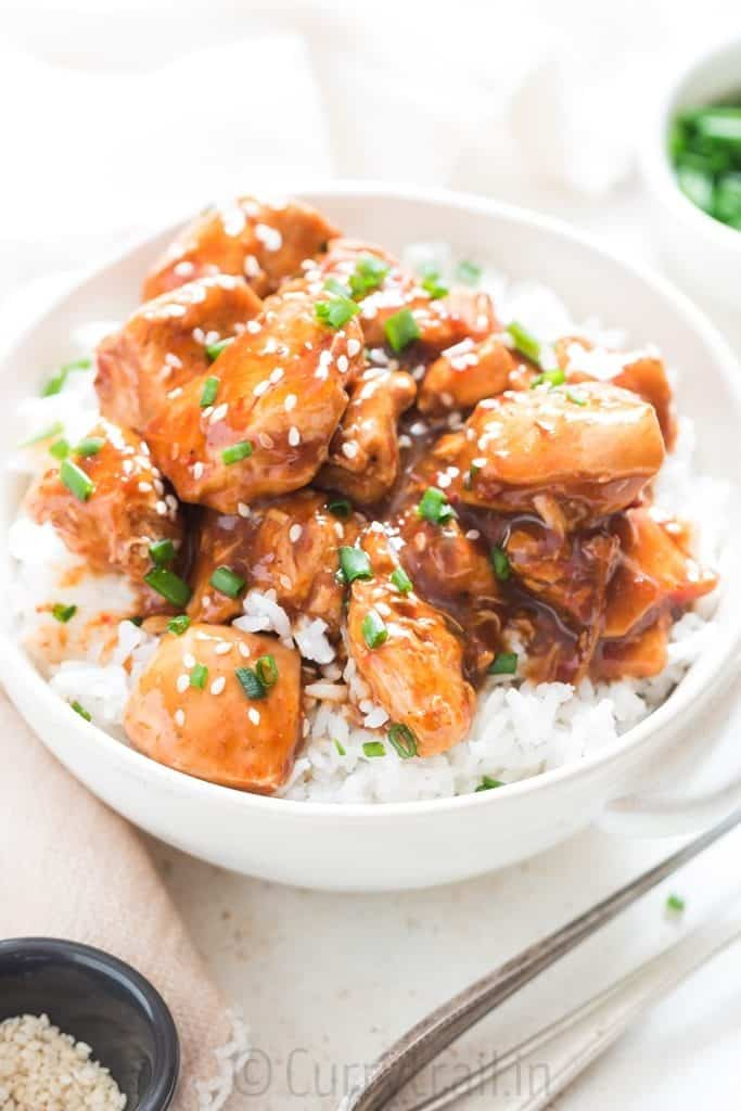 delicious instant pot General Tso chicken over rice in white bowl garnished with chives