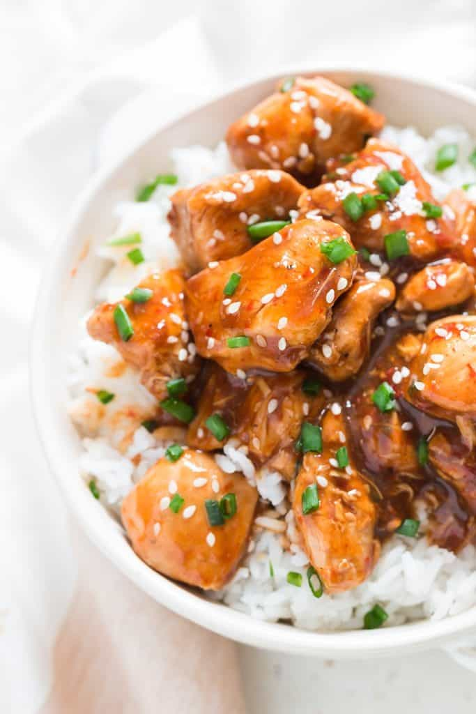 General Tso chicken over a bowl of rice in white bowl