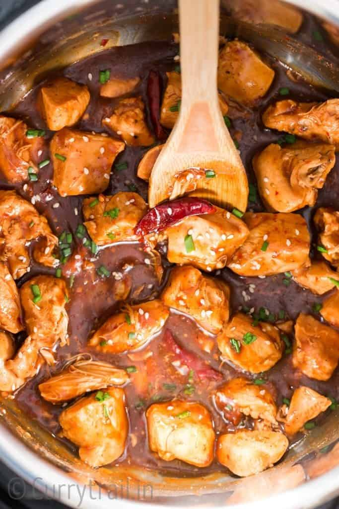 delicious General Tso chicken cooked in instant pot with wooden spatula in it
