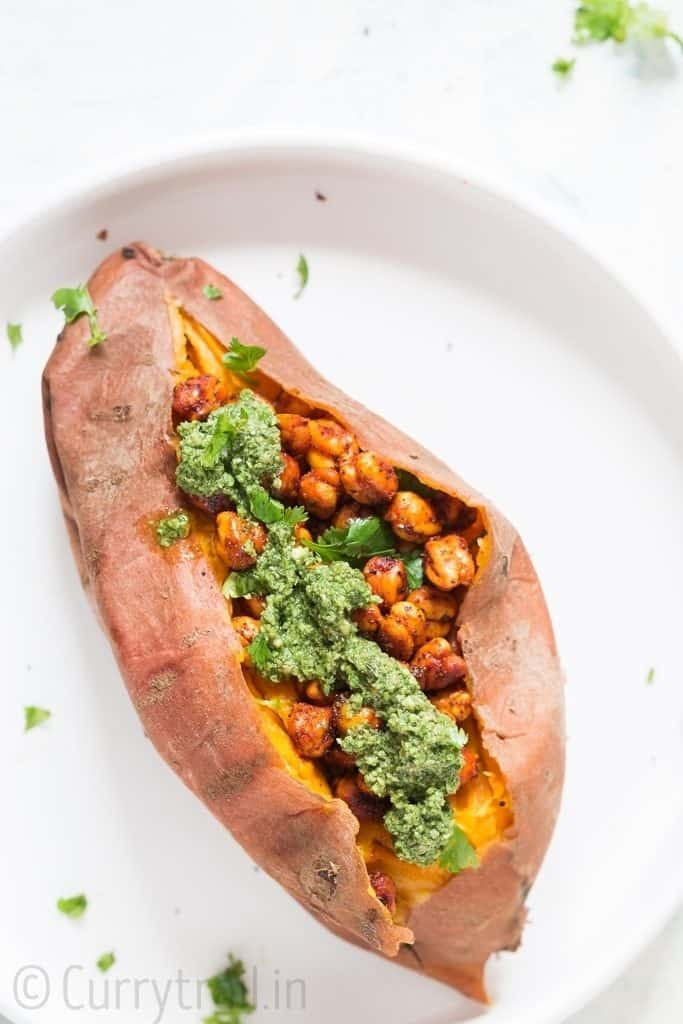 sweet potatoes stuffed with spicy chickpeas and pesto in the center placed on white plate