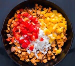 Red and yellow bell peppers added to pan