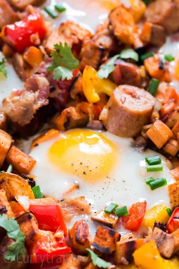 sweet potato breakfast hash with vegetables sausages and eggs cooked in cast iron skillet