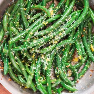 garlic sauteed green beans sprinkled with Parmesan and lemon zest Thanksgiving side dish cooked in skillet