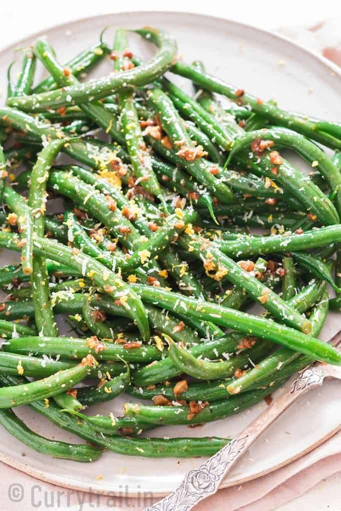 garlic sauteed green beans sprinkled with Parmesan and lemon zest Thanksgiving side dish on white ceramic plate