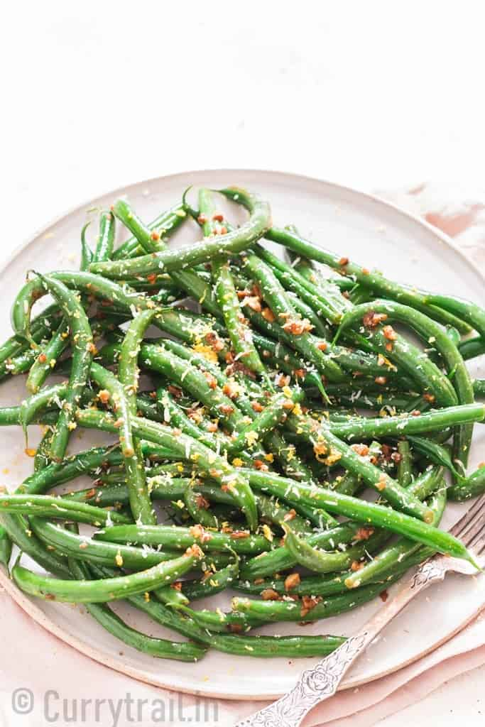 garlic sauteed green beans sprinkled with Parmesan and lemon zest served on ceramic plate