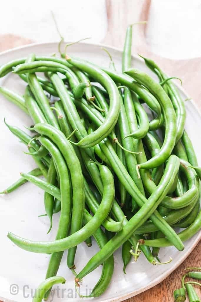 fresh green beans on white plate