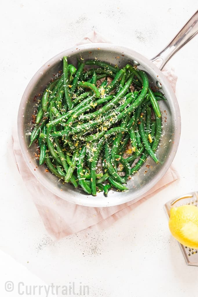 garlic sauteed green beans sprinkled with Parmesan and lemon zest served in skillet