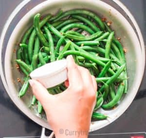 adding lemon juice to sauteed green beans in skillet