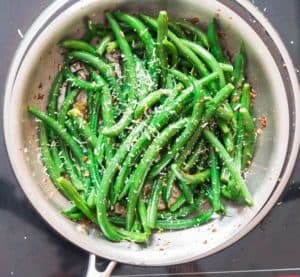 sauteed green beans garnished with lemon zest and Parmesan sauce