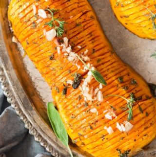 hasselback butternut squash drizzled with honey butter sauce and garnished with nuts and herbs