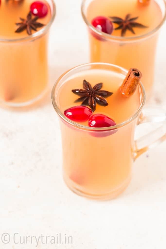 three cups of Instant pot spiced apple cider with fresh cranberries cinnamon stick and star anise garnish