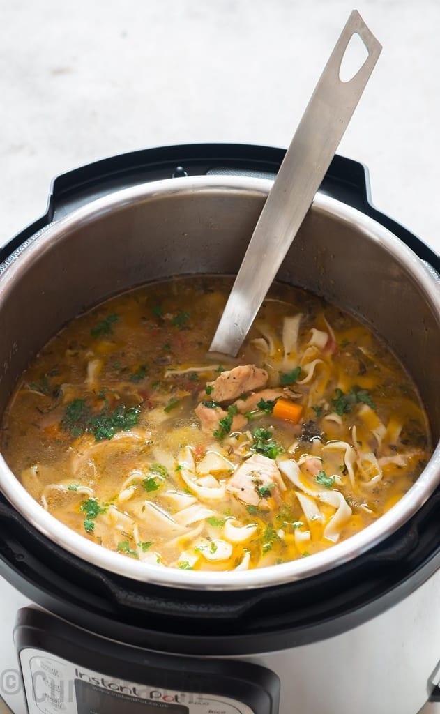instant pot chicken noodles soup inside pot with soup ladle