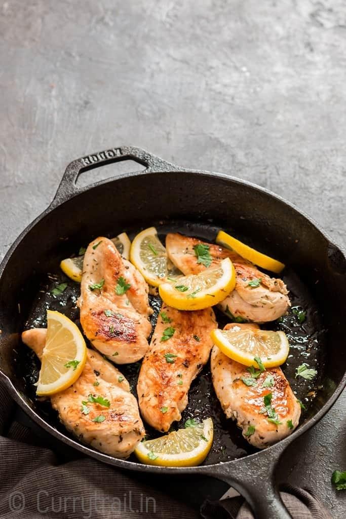 lemon chicken in cast iron skillet with parsley garnish
