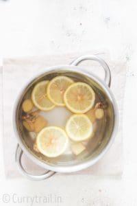 Steeping fresh ginger and lemon slices in hot water for honey lemon ginger tea