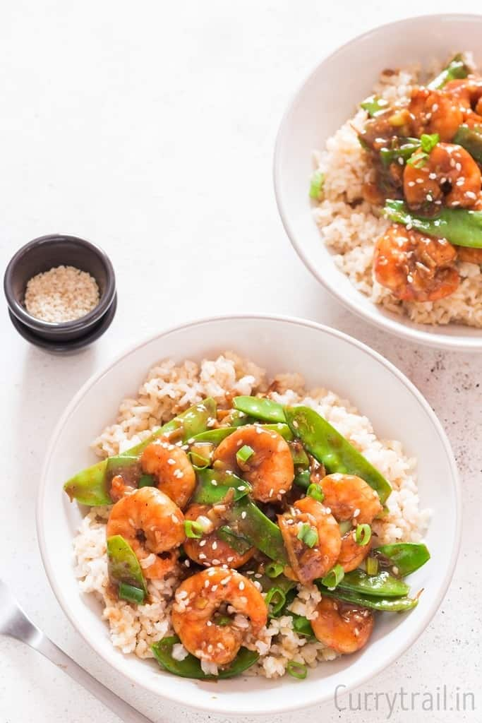 two bowls of rice with stir fried shrimp on top