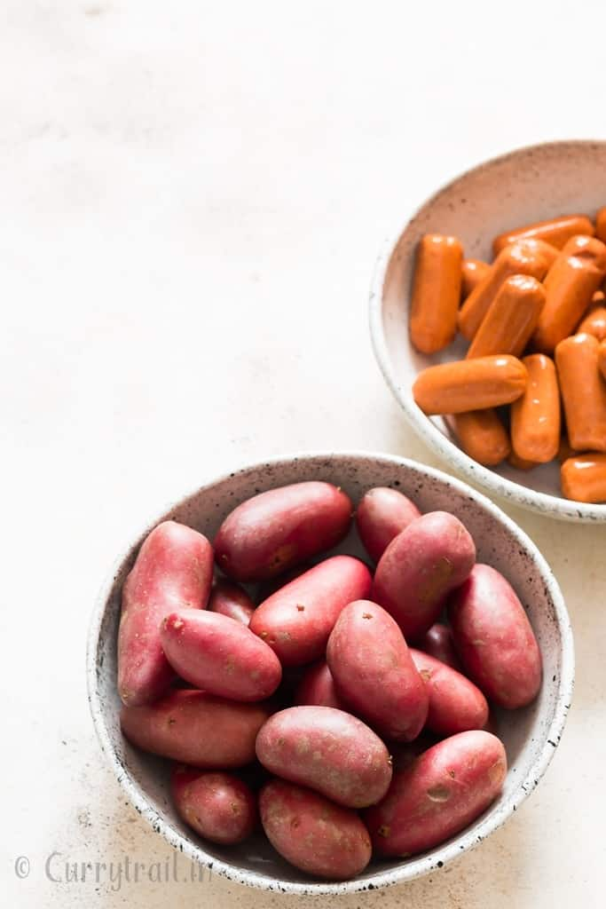 red potatoes and sausages in two white bowls
