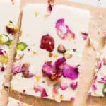 white chocolate bark with dried rose petals, pistachios and dried strawberries on parchment paper