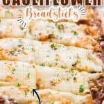 cheesy cauliflower breadsticks on baking tray with text